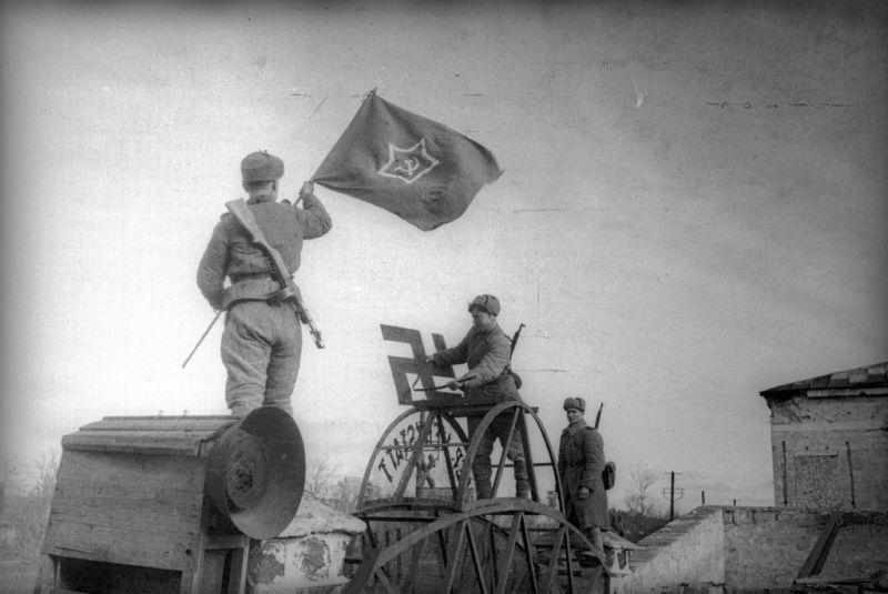 Бойцы РККА сбивают свастику с ворот завода в Керчи, фото Е. Халдея