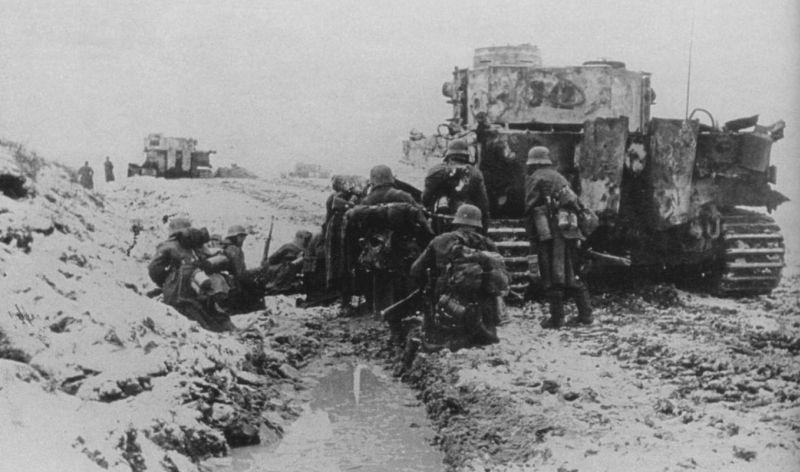 Немцы укрываются за танком во время боев за город