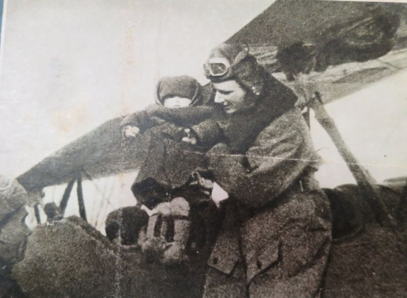 Александр Петрович усаживает ребёнка в кабину самолета