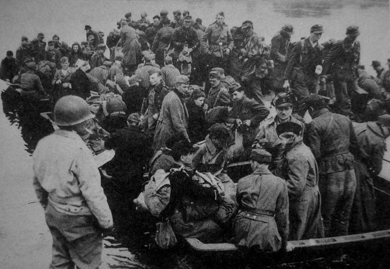 Немецкие солдаты и офицеры, в том числе женщины, призванные на военную службу, пересекают Эльбу, чтобы сдаться в плен американцам