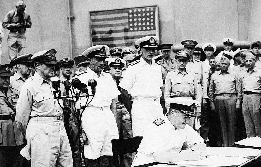 Продуманный антураж для подписания акта о капитуляции Японии на борту линкора «Миссури»: на заднем плане – флаг коммодора Мэттью Перри, под дулом пушек принудившего Японию к подписанию первого договора с США «О мире и дружбе» 1854 года. Акт подписывает представитель Великобритании адмирал Брюс Фрэзер. Крайний слева – генерал армии США Дуглас Макартур
