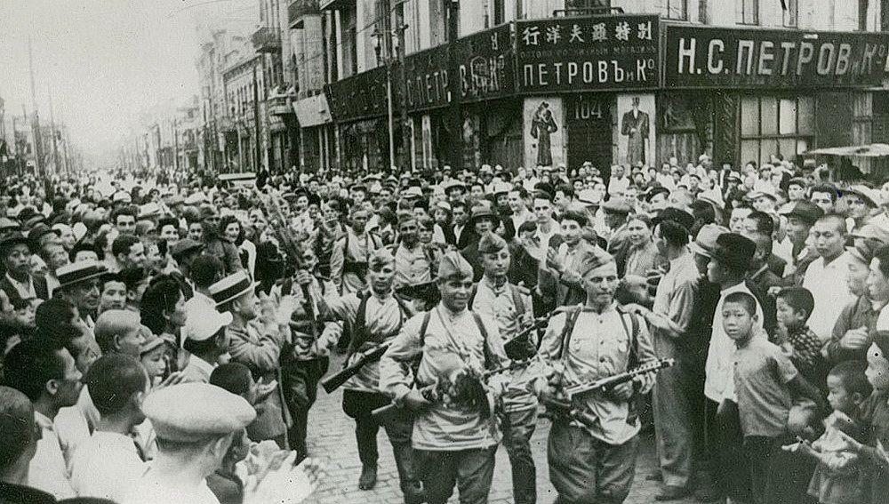 Жители Харбина (Китай) приветствуют вступающие в город части РККА. 19 августа 1945 года Харбин был занят советским воздушным десантом 9-й воздушной армии 1-го Дальневосточного фронта и моряками Амурской военной флотилии 2-го Дальневосточного фронта, а 20 августа в город вступили соединения 15-й армии 2-го Дальневосточного фронта