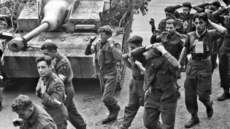 Пленные британские десантники из 1-й воздушно-десантной дивизии идут мимо немецкой САУ StuG III в Арнеме (Голландия)